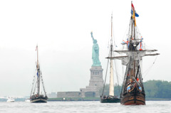 Historic sailing ships with the Statue of Liberty in the background