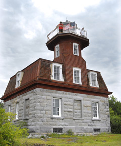 lighthouse with a grey stone base and red shingled top