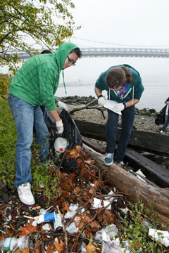Volunteer pick up trash on the shore near a bridge