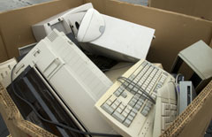 A cardboard box containing electronic waste