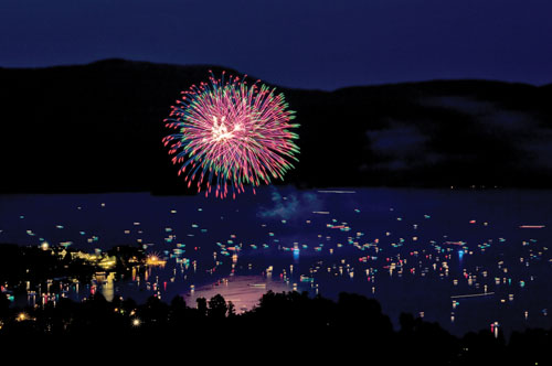Fireworks at night over Bolton Landing, reflected in the water