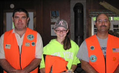 Two sportsman's ed instructors in orange vests flank a junior instructor