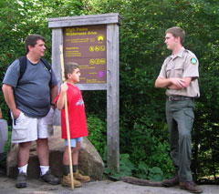A DEC forester talking with hikers on a trail