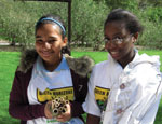 Two girls in green horizons t-shirts make bee habitat