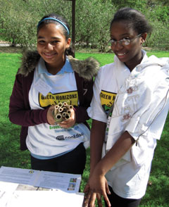 Two Green Horizons students with materials for making a bee habitat.