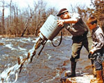 A man emptying fish into a stream from a large gray bucket