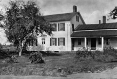 A black and white photo of an old farm house