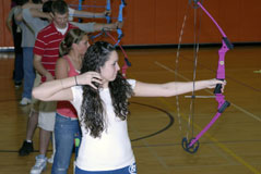 A line of students practice archery in a gym