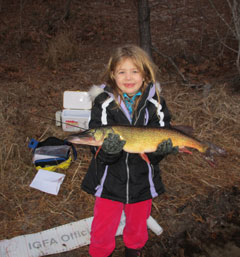A young girl in red pants holds alarge chin pickerel