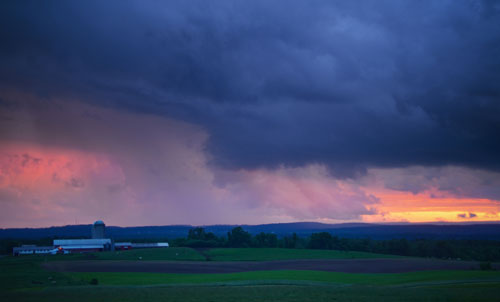 A sunset is hidden by an approaching storm over agricultural land
