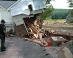 Part of a house is torn away and the foundation destroyed by flood waters