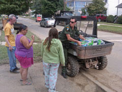 An ECO unloads bottled water for residents waiting on the sidewalk.