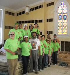 Flood relief volunteers in green t-shirts standing inside a church