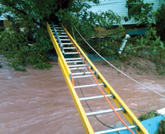A yellow ladder with ropes spans a raging creek