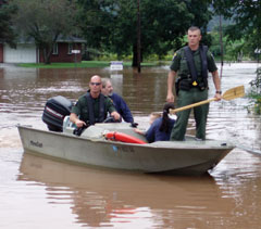 Two ECOs (one standing) in a boat carying flood victims through the flood waters