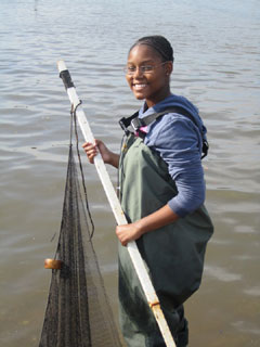 A young black woman holds a sampling net