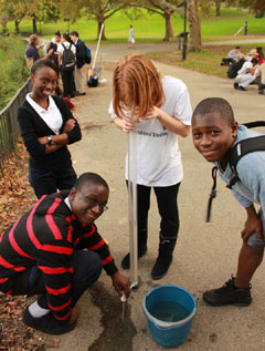 Four students in a park looking at water samples
