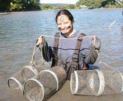 A young woman wearing waders and face paint stands in the river holding three cylindrical wire mesh traps