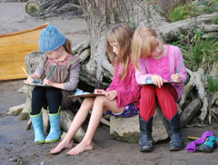 Three girls sitting on tree roots writing on clip boards