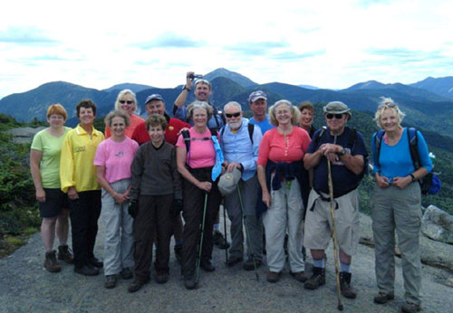 A group of hikers pose for a photograph on top of an Adirondack peak