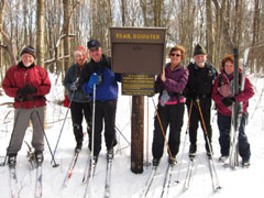 A group of cross-country skiiers at a trailhead
