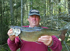 A man holding out a large brook trout