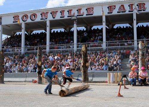 Log rolling competition passes in front of the grandstand