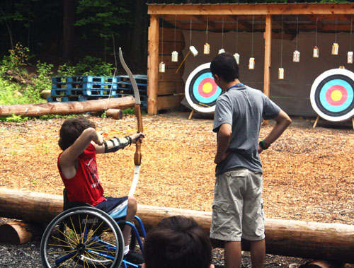 A child in a wheelchair aims a bow and arrow at a target