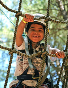 A young boy in a helmet climbs a rope ladder