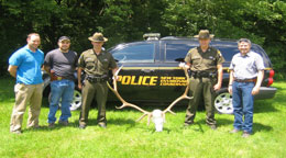 Game wardens and ECos pose with a large elk skull and antlers