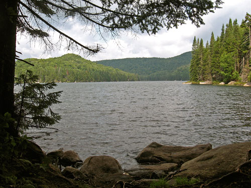 A view across a lake surrounded by wooded hills