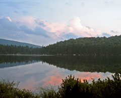 A pink clouds reflected in a lake in the mountains