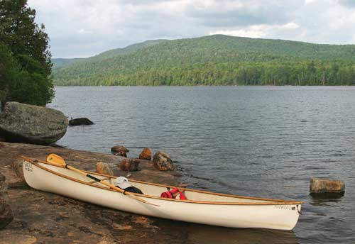 Canoe on shore at lake side
