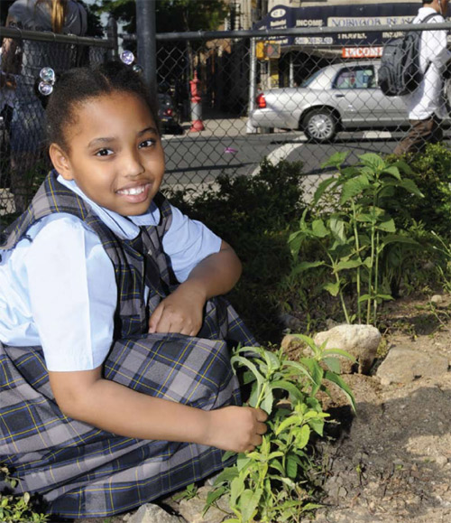 A young girl in the After School Conservation Club learns about plants
