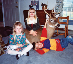 Three children in a house with a stuffed deer