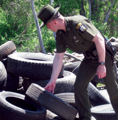 An officer at a waste tire dump