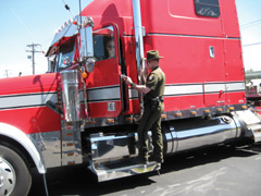An ECo talking to the driver of a red trailer truck