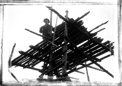 A man standing on an early fire tower platform made of wood