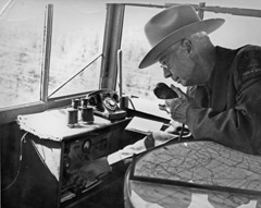 A fire tower observer with map, radio, binoculars and phone