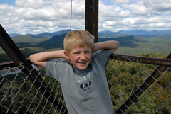 A young blond boy leaning against the fire tower railing at the top