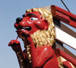A red painted carved lion from the front of a boat