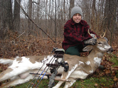 A young hunter poses with a piiebald deer he shot