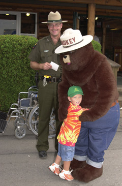 A little boy gives Smoeky the Bear a hug