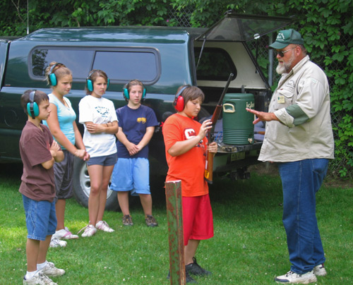 A hunter safety instructor in an outdoor class with five students