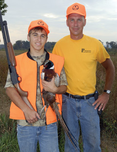 An adult with a youth hunter who is holding a pheasant
