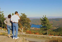 Hikers enjoying the view of a lake and fall foliage from high on a mountain