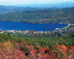 View of a blue lake and lakeshore towns seen from a mountain in fall.