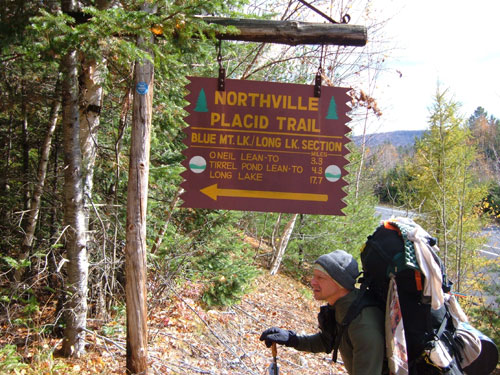 A hiker with a large backpack starts on the trail