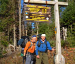 Two male hikers stand at one end of the Northville-Placid trail below the sign