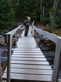 A hiker crossing a stream on a wooden bridge